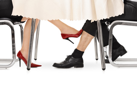 Photo pour Close-up on a woman touching a guy under a table with her foot isolated on white background - image libre de droit