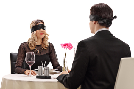 Photo pour Young man and woman sitting on a blind date at a restaurant isolated on white background - image libre de droit