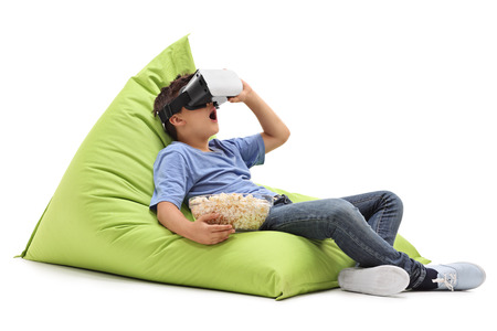 Photo pour Amazed little boy looking in VR goggles and eating popcorn seated on a beanbag isolated on white background - image libre de droit