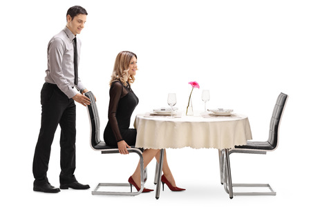 Photo for Young gentleman helping his girlfriend with the chair at a restaurant table isolated on white background - Royalty Free Image