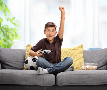 Foto de Joyful kid playing football video game and celebrating a goal with his fist in the air seated on a gray sofa - Imagen libre de derechos