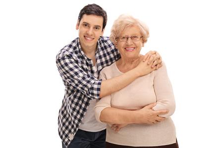 Foto de Studio shot of a young man hugging a senior lady isolated on white background - Imagen libre de derechos