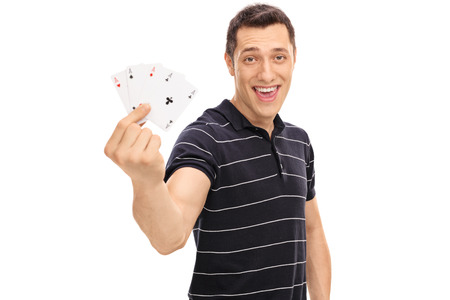 Lucky guy holding four aces and looking at the camera isolated on white background