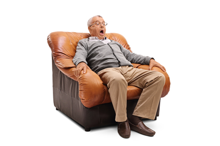 Photo pour Scared senior with a terrified facial expression sitting on an armchair isolated on white background - image libre de droit