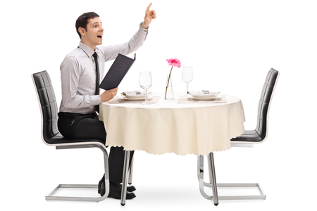 Foto de Young man calling the waiter and sitting at a restaurant table isolated on white background - Imagen libre de derechos