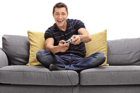 Foto de Cheerful young man seated on a sofa playing video games isolated on white background - Imagen libre de derechos