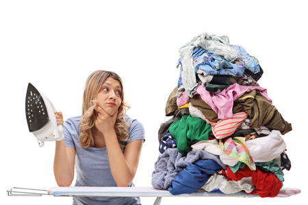 Photo pour Sad young woman holding an iron and looking at a big pile of clothes isolated on white background - image libre de droit