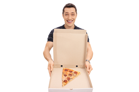 Happy guy showing a pizza box with one piece of pizza isolated on white background
