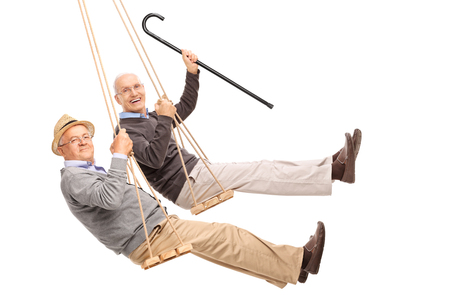 Photo pour Two cheerful elderly men swinging on wooden swings isolated on white background - image libre de droit