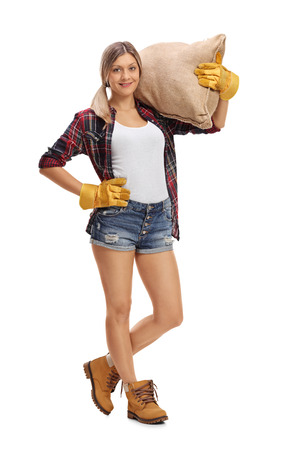 Full length portrait of a female farmer posing with a burlap sack isolated on white background