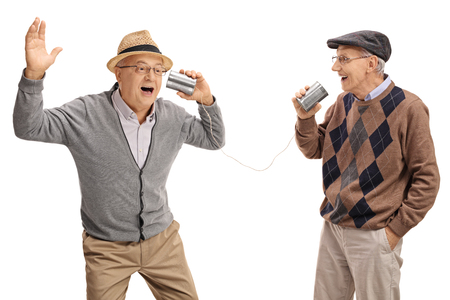 Cheerful seniors telling jokes to each other through a tin can phone isolated on white background