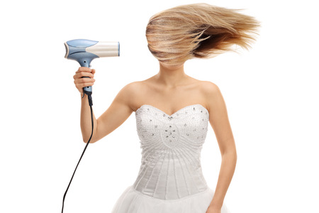 Photo for Bride blowing her hair with a hair dryer isolated on white background - Royalty Free Image