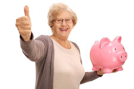 Photo pour Cheerful senior holding a piggybank and making a thumb up sign isolated on white background - image libre de droit