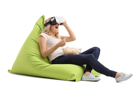Photo pour Amazed woman seated on a beanbag using a VR headset and eating popcorn isolated on white background - image libre de droit