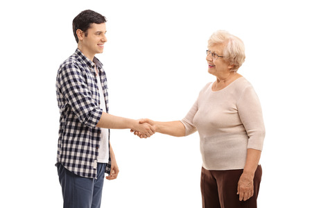 Photo for Young man shaking hands with an elderly woman isolated on white background - Royalty Free Image