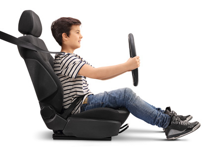 Photo pour Boy sitting on a car seat and holding a steering wheel pretending to drive isolated on white background - image libre de droit