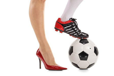 Photo pour Woman with one foot in a high-heeled shoe and other in a soccer shoe pressing a football isolated on white background - image libre de droit