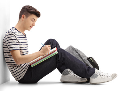 Photo pour Teen student writing in a notebook and leaning against a wall isolated on white background - image libre de droit