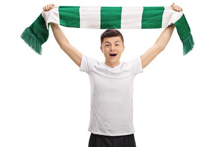 Overjoyed teenage football fan holding a scarf isolated on white background