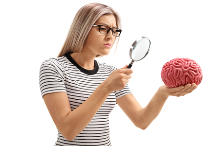 Young woman examining a brain model with a magnifying glass isolated on white background