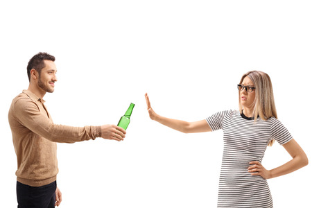 Young woman refusing a bottle of beer isolated on white background