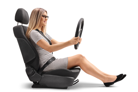 Young woman sitting in a car seat and holing a steering wheel isolated on white background