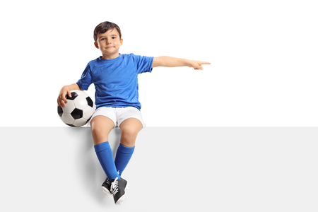 Photo pour Little footballer sitting on a panel and pointing isolated on white background - image libre de droit