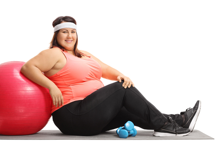 Foto de Overweight woman sitting on an exercise mat and leaning on a pilates ball isolated on white background - Imagen libre de derechos