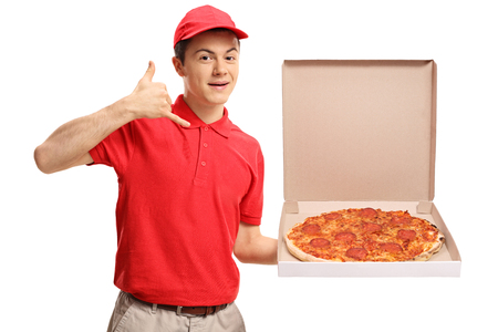 Photo pour Teenage pizza delivery boy holding a pizza box and making a call me gesture isolated on white background - image libre de droit