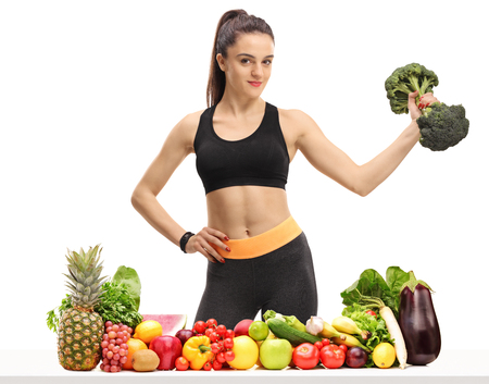 Foto de Fitness woman with a broccoli dumbbell behind a table with fruit and vegetables isolated on white background - Imagen libre de derechos
