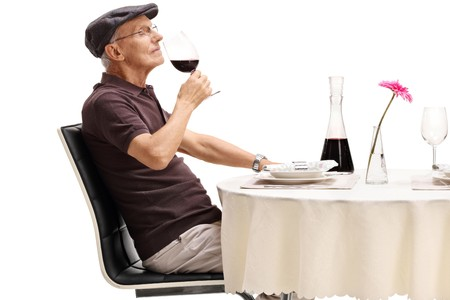 Senior seated at a restaurant table smelling a glass of red wine isolated on white background