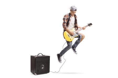 Teenage boy with an electric guitar plugged in an amplifier jumping isolated on white background