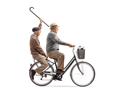 Joyful seniors with a cane and a football riding a bicycle together isolated on white background