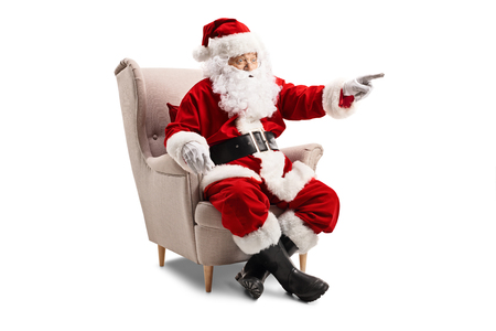 Photo pour Santa Claus sitting in an armchair and pointing - image libre de droit