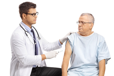 Foto de Young doctor vaccinating a mature male patient isolated on white background - Imagen libre de derechos