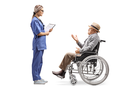 Full length profile shot of a young female nurse talking to an elderly gentleman in a wheelchair isolated on white background