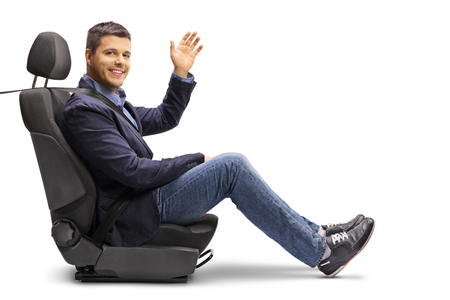 Photo pour Full length shot of a young man in a car seat with a fastened seatbelt holding a steering wheel isolated on white background - image libre de droit
