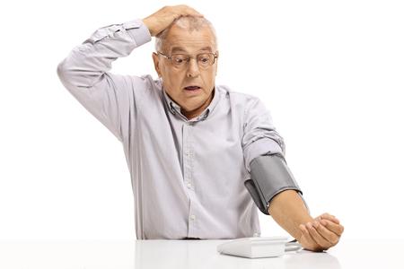 Foto de Shocked mature man taking blood pressure measurement isolated on white background - Imagen libre de derechos