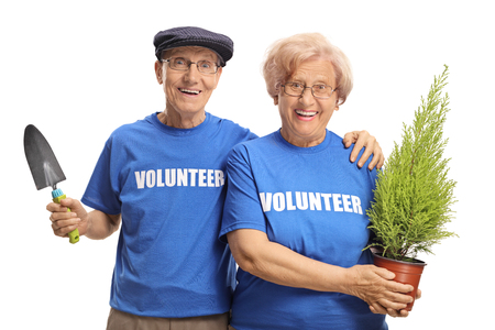 Foto de Senior man and woman volunteers holding a plant and a spade for planting isolated on white background - Imagen libre de derechos