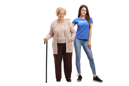 Photo pour Full length portrait of an elderly woman with a cane and a young female volunteer isolated on white background - image libre de droit