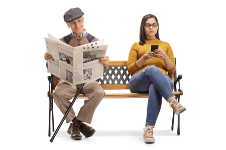 Photo for Full length portrait of a young female with a mobile phone and a senior man reading a newspaper on a bench isolated on white background - Royalty Free Image