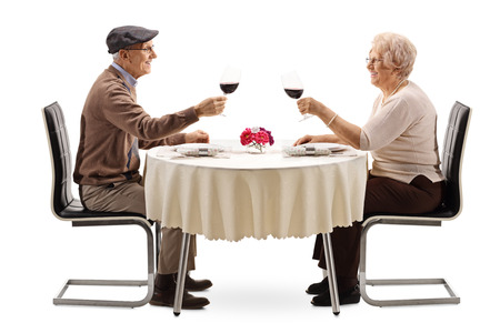 Photo pour Elderly man and woman making cheers with red wine at a table isolated on white background - image libre de droit