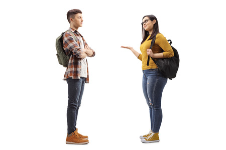 Photo pour Full length profile shot of female student talking to a male student friend isolated on white background - image libre de droit