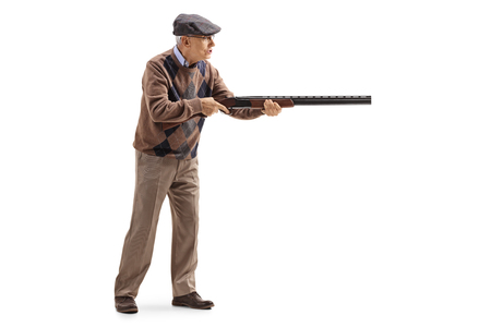 Photo for Full length profile shot of an elderly man aiming with a shotgun isolated on white - Royalty Free Image