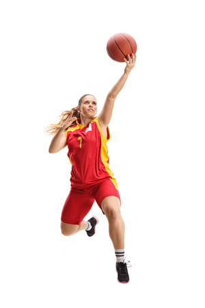 Photo for Full length portrait of a female basketball player jumping with a ball isolated on white - Royalty Free Image