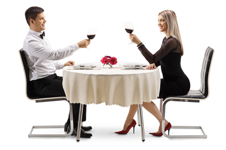Photo for Young elegant couple toasting with wine at a table isolated on white background - Royalty Free Image