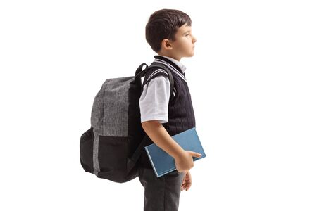 Photo pour Profile view of a schoolboy in a uniform and a backpack isolated on white background - image libre de droit