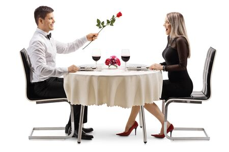 Foto de Full length profile shot of a young man giving a red rose to a young woman at a restaurant table isolated on white background - Imagen libre de derechos