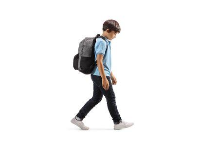 Foto de Full length profile shot of a sad schoolboy walking with his hand down isolated on white - Imagen libre de derechos