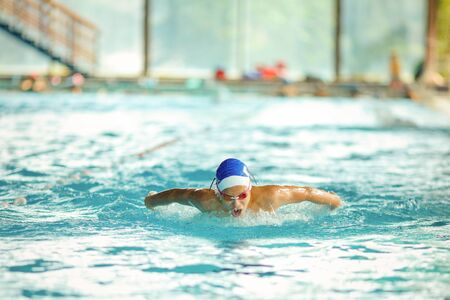 Photo pour Young male swimmer swimming in a pool - image libre de droit